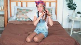 La muchacha se sienta en cama, trenza su pelo en trenzas, sonrisa, mira la cámara, cámara lenta almacen de video