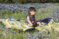 La muchacha se sienta en campo del Bluebonnet foto de archivo libre de regalías