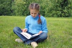 La muchacha se sienta en campo verde y lee el libro Fotos de archivo