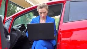 La muchacha se sienta en coche con las puertas abiertas Ella bebe el café de la taza y la mirada en la pantalla del ordenador por metrajes