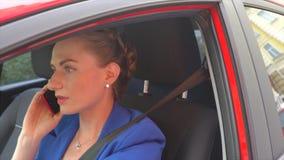 La muchacha se sienta en coche y habla en el teléfono Ella stucked en tráfico La mujer está trastornada y enojada Ella se queja metrajes