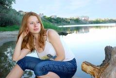 La muchacha se sienta en costa imagen de archivo libre de regalías