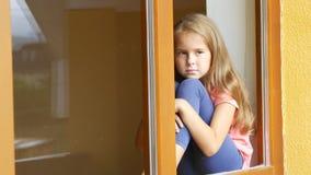 La muchacha se sienta en el alféizar y mira hacia fuera la ventana almacen de metraje de vídeo