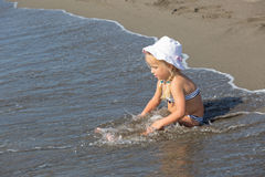 La muchacha se sienta en el borde del agua Imagen de archivo