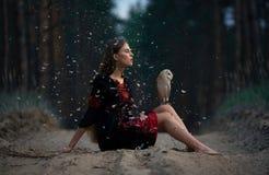 La muchacha se sienta en el camino forestal con el búho en sus rodillas entre fluf del vuelo Imagen de archivo