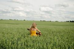 La muchacha se sienta en el campo de la guitarra de los juegos del centeno Fotos de archivo
