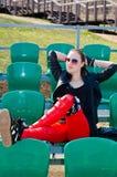La muchacha se sienta en el estadio Foto de archivo