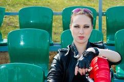 La muchacha se sienta en el estadio Imagen de archivo libre de regalías
