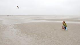 La muchacha se sienta en el Norte-Mar Foto de archivo libre de regalías