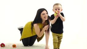 La muchacha se sienta en el piso, al lado de las verduras miente, ella intenta detener al bebé Fondo blanco Cámara lenta metrajes