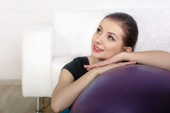 La muchacha se sienta en el piso después de ejercitar Imagen de archivo libre de regalías