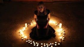 La muchacha se sienta en el piso entre las velas ardientes metrajes