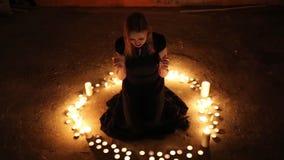 La muchacha se sienta en el piso entre las velas ardientes almacen de video