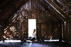 La muchacha se sienta en la entrada Granero de madera con puntos culminantes hermosos del sol Objeto del arte en el parque del ar imagen de archivo
