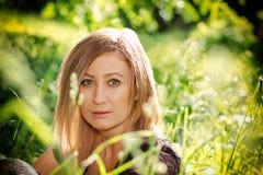 La muchacha se sienta en hierba Fotos de archivo libres de regalías