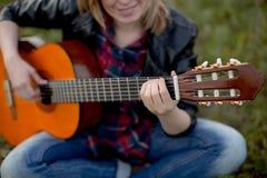 La muchacha se sienta en la hierba con jugar de la guitarra Fotografía de archivo