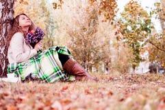 La muchacha se sienta en la hierba del otoño, leyendo un libro Foto de archivo