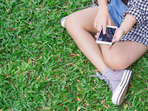 La muchacha se sienta en hierba verde en el smartphone del juego del parque Fotos de archivo libres de regalías