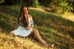 La muchacha se sienta en hierba y presenta Fotos de archivo