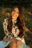 La muchacha se sienta en hierba y presenta Fotos de archivo libres de regalías