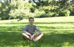 La muchacha se sienta en la hierba Fotografía de archivo libre de regalías