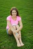 La muchacha se sienta en la hierba Imagen de archivo