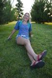 La muchacha se sienta en la hierba en el parque Imagenes de archivo