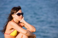 La muchacha se sienta en la playa del mar azul Imagen de archivo