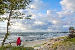 La muchacha se sienta en la playa que mira al horizonte Imágenes de archivo libres de regalías