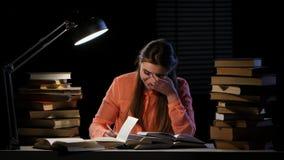 La muchacha se sienta en la tabla y la lectura de un libro Fondo negro Lapso de tiempo metrajes