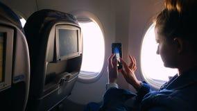 La muchacha se sienta en la ventana del avión y toma una imagen de la ventana almacen de video