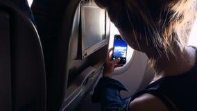 La muchacha se sienta en la ventana del avión y toma una imagen de la ventana almacen de metraje de vídeo