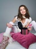 La muchacha se sienta en las almohadillas con el corazón en sus manos Foto de archivo libre de regalías