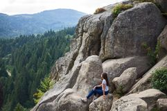 La muchacha se sienta en las rocas Foto de archivo libre de regalías