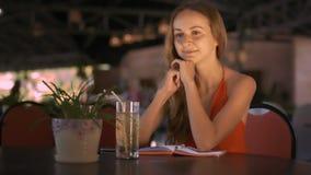 La muchacha se sienta en las sonrisas de la tabla que escucha la historia del amigo