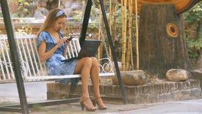 La muchacha se sienta en los textos del oscilación en smartphone en parque metrajes