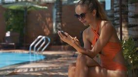 La muchacha se sienta en lugar sombrío en la piscina y textos en el teléfono