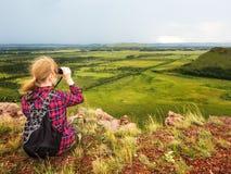 La muchacha se sienta en la montaña y mira en la distancia con los prismáticos imagen de archivo libre de regalías