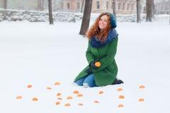 La muchacha se sienta en nieve entre los mandarines en el día de invierno Imagen de archivo