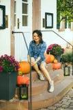 La muchacha se sienta en pasos con las calabazas en Halloween Imágenes de archivo libres de regalías