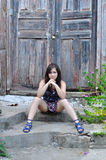 La muchacha se sienta en pasos de progresión cerca de una puerta vieja Imagen de archivo libre de regalías