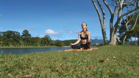 La muchacha se sienta en la posición de la yoga respecto a hierba verde por el río
