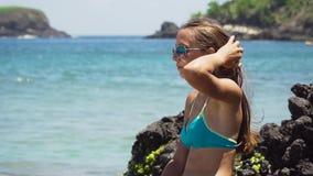 La muchacha se sienta en la roca y mira el mar Bali, Indonesia metrajes