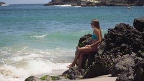 La muchacha se sienta en la roca y mira el mar Bali, Indonesia almacen de metraje de vídeo