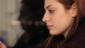 La muchacha se sienta en travesaño de la ventana y smartphone con almacen de metraje de vídeo