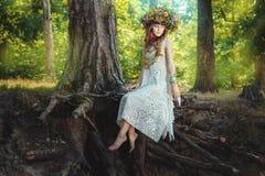 La muchacha se sienta en un árbol en el bosque de hadas fotos de archivo libres de regalías