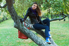 La muchacha se sienta en un árbol en parque Fotos de archivo libres de regalías