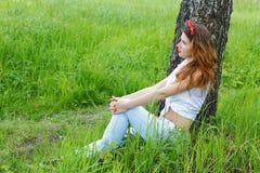 La muchacha se sienta en un abedul en bosque Foto de archivo libre de regalías
