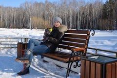 La muchacha se sienta en un banco en el parque Imagen de archivo
