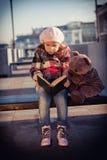 La muchacha se sienta en un banco y lee el libro imagen de archivo libre de regalías